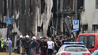 Police and rescue teams stand outside an apparently vacant office building where a small plane crashed in the Milan suburb of San Donato, October 3, 2021.
