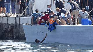 Un homme demande de l'aide, sur l'île italienne de Lampedusa, Italie, le 3 octobre 2021