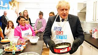 Britain's Prime Minister Boris Johnson and Home Secretary Priti Patel try baking during a visit to HideOut Youth Zone, in Manchester, England, Sunday Oct. 3, 2021.