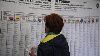 امرأة تنظر إلى أسماء المرشحين وشعارات الحزب في مركز اقتراع في تورينو بإيطاليا.