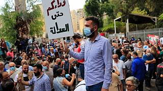 متظاهر يحمل لافتة خارج مبنى المحكمة خلال مظاهرة تضامن مع القاضي طارق بيطار في بيروت، لبنان.