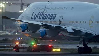 A Lufthansa Boeing 747 with covered engines is pulled to a parking position at the airport in Frankfurt, Germany, Oct. 22, 2020.