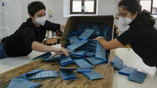 Scrutineers count ballots after the closing of a polling station, in Rome, Monday, Oct. 4, 2021.