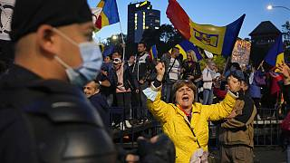 A woman shouts during an anti-government and anti-restrictions protest organized by the far-right Alliance for the Unity of Romanians or AUR, in Bucharest, Romania, Saturday,
