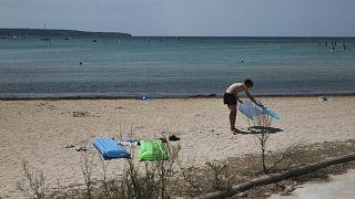 A sunbather enjoys the beach in the Balearic Islands capital of Palma de Mallorca, Spain, July 29, 2020.
