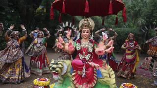 Gujarati women in traditional attire practise the Garba dance, around an idol of goddess Ambe ahead of Hindu festival of Navratri in Ahmadabad, India, Friday, Oct. 1, 2021.