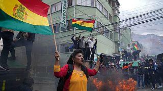 مزارعو كوكا مناهضون للحكومة يرفعون الأعلام البوليفية خلال اشتباكات مع الشرطة بالقرب من سوق الكوكا في لاباز، الإثنين 4 أكتوبر 2021