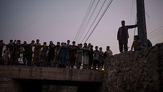 أفغان يتجمعون لمشاهدة مقاتلي طالبان وهم يحتجزون متعاطي المخدرات خلال عملية للشرطة في كابول، الجمعة 1 أكتوبر 2021