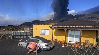Imagen de una vivienda parcialmente cubierta con ceniza volcánica y el volcán Cumbre Vieja al fondo, en la isla de La Palma.