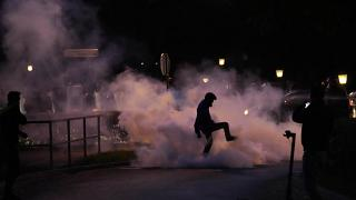 A demonstrator stomps on a smoke canister during the protest in Ljubljana.
