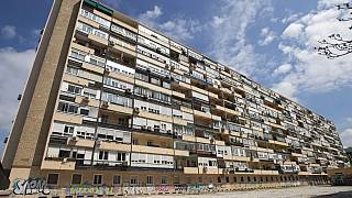 FILE - In this April 8, 2020 file photo, a man walks in front of a large apartment block in Madrid, Spain.
