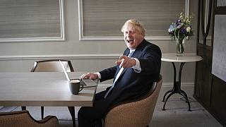 In this Oct. 5, 2021, file photo, Britain's Prime Minister Boris Johnson prepares his keynote speech in his hotel room in Manchester, England,