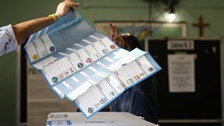 A man receives his ballots at a polling station in Rome.