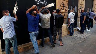 مودعون يدقون على الجدران المعدنية لأحد البنوك خلال احتجاج في بيروت، الأربعاء 6 أكتوبر 2021