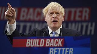 Britain's Prime Minister Boris Johnson gestures as he makes his keynote speech at the Conservative party conference in Manchester, England, Wednesday, Oct. 6, 2021.