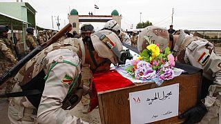 صورة من الارشيف - جنود عراقيون يقبلون نعشاً يحمل رفات جندي عراقي عند المعبر الحدودي العراقي الإيراني في الشلامجة، العراق