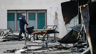 A police officer walks past burned hospital equipment on the site of the fire.