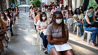 نساء ينتظرن دورهن لتلقي لقاح فايزر في مركز التطعيم في ريو دي جانيرو، البرازيل.