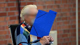 Defendant Josef S hides his face behind a folder as he waits for the start of his trial in Brandenburg an der Havel, northeastern Germany, on October 7, 2021.