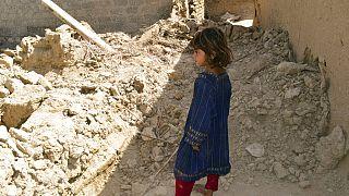 Une fillette regardant une maison endommagée après le tremblement de terre à Harnai, à environ 100 kilomètres à l'est de Quetta, au Pakistan, jeudi 7 octobre 2021.