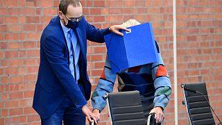 يتلقى المدعى عليه يوزف شوتز المساعدة من محاميه ستيفان ووتركامب أثناء وصوله لمحاكمته في براندنبورغ آن دير هافيل، شمال شرق ألمانيا، 7 أكتوبر 2021