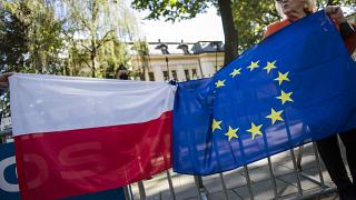 Protesters hold Polish and EU flags tied together during a demonstration outside the Constitutional Tribunal.