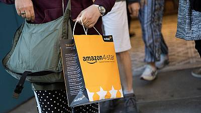 A customer carries a bag as they leave a new Amazon store where everything for sale is rated 4 stars and above.