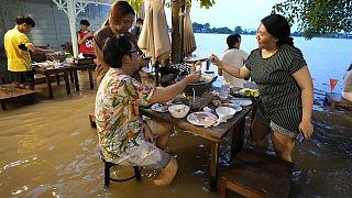 شاهد: رواد مطعم في تايلند يستمتعون بتناول الطعام في الماء بعد الأمطار الموسمية