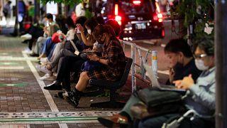 أناس يقبعون في الشارع خارج محطة قطار بعد الزلزال الذي ضرب طوكيو. 2021/10/07