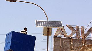 صورة من تلارشيف -  تعديل لوح شمسي متصل بأعلى عمود كهرباء على طريق رئيسي في منطقة الكرادة ببغداد