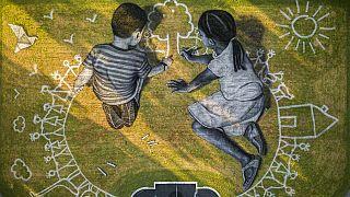 A francia művész, Saype 6000 nm-es tájrajzra, melyen két kisgyerek rajzol - az alkotást az ENSZ genfi székhelye mellett készítették el 2020-ban