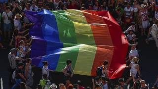 Participants of the annual LGBT+ pride parade carry the rainbow flag in Madrid.