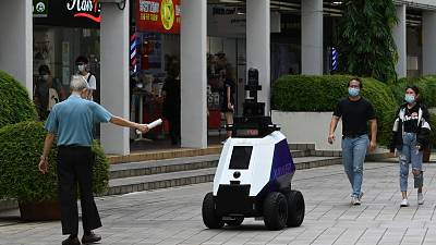 """A man gestures to an autonomous robot named """"Xavier"""" as it patrols a shopping and residential district in Singapore."""