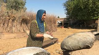 Qahwa, a Syrian mother of eight, is baking the traditional tannour bread.