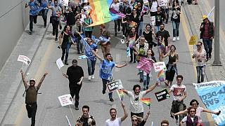 Protesters hold signs and a rainbow flag during a demonstration in Ankara in May 2019.