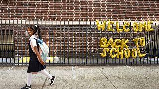 Mädchen mit Maske auf dem Weg in die Schule in New York