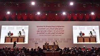 الممثل الأمريكي الخاص للمصالحة في أفغانستان، زلماي خليل زاد والشريك المؤسس لحركة طالبان الملا عبد الغني بردار يوقعان اتفاقية سلام في العاصمة القطرية الدوحة. أرشيف