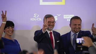 Petri Fiala, a hárompárti Együtt koalíció vezetője (középen) ünnepel az eredményvárón Prágában