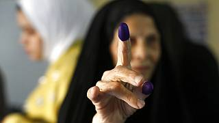 An Iraqi elderly woman shows her ink-stained finger after casting her vote inside a polling station in the country's parliamentary elections in Baghdad, Iraq, Sunday, Oct. 10,