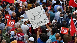 تونسيون يرفعون الأعلام الوطنية خلال مسيرة ضد رئيسهم على طول شارع الحبيب بورقيبة في العاصمة تونس في 10 أكتوبر 2021.