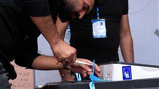 موظف يفتح أحد صناديق الاقتراع في بغداد