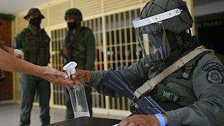 Un soldado echa desinfectante en las manos de un participante en el simulacro electoral en El Valle, Caracas
