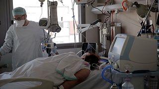 ممرض يعتني بمريضة في وحدة العناية المركزة في مستشفى شارل نيكول، في روان، فرنسا.