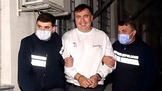 Georgian Police officers escort former President Mikheil Saakashvili after he was arrested in Rustavi.