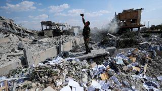 جندي سوري يصور الأضرار التي لحقت بمركز البحث العلمي السوري الذي تعرض لهجوم عسكري أمريكي وبريطاني وفرنسي لمعاقبة الرئيس بشار الأسد للاشتباه بهجوم كيماوي ضد المدنيين في برزة قرب