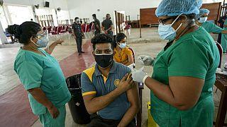 A Sri Lankan university student receives his coronavirus vaccine at the Sri Jayawardenapura university in Colombo, Sri Lanka, Monday, Oct. 11, 2021.