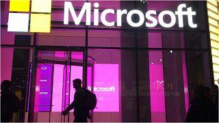 أشخاص يسيرون بجانب مكتب شركة مايكروسوفت في مدينة نيويورك بالولايات المتحدة الأمريكية