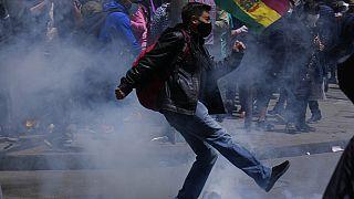 Un manifestante da una patada a un proyectil de gases lacrimógenos en La Paz, Bolivia
