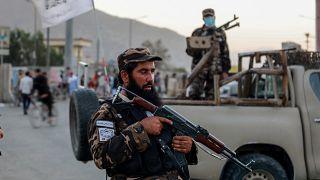 Tálib fegyveresek az Eid Gah mecset kapujánál, ahol ismeretlen elkövetők pokolgépet robbantottak 2021. október 3-án.