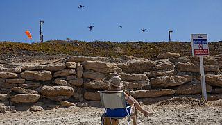 Áruszállító drónokat néz egy nyaraló Tel Aviv tengerpartján
